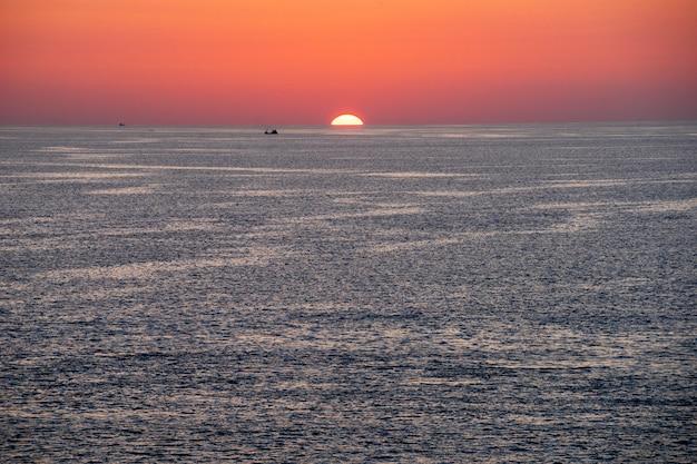 Sonnenuntergangansicht vom promthep-kap, phuket-insel, südthailand, mit schönem oranghimmel und kleinem fischerboot und yacht.
