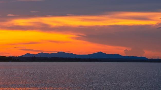Sonnenunterganghimmel und große sonne über dem see.