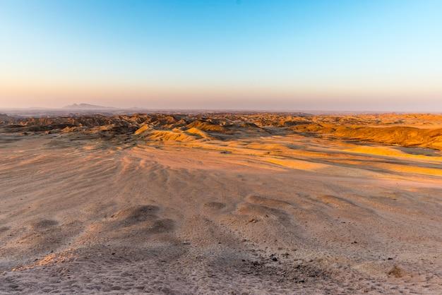 Sonnenunterganglicht über unfruchtbaren tälern und schluchten, namibia