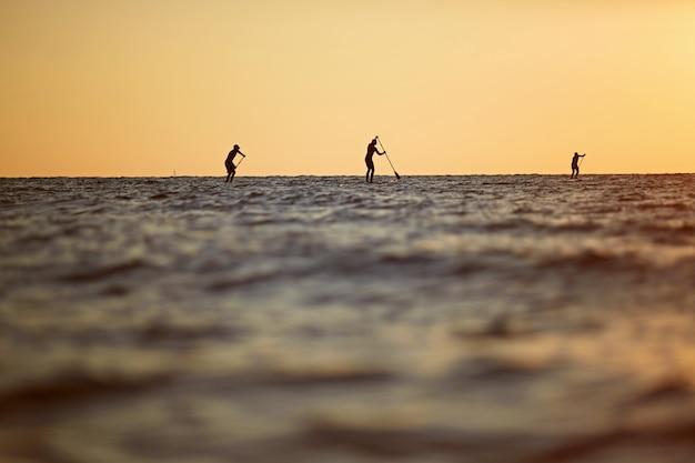 Sonnenuntergangschattenbild von drei jungen leuten, die auf einem surfbrett zum horizont im schönen szenischen sonnenuntergang der hohen see rudern