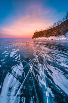 Sonnenuntergangshimmel mit natürlichem brechendem eis über gefrorenem wasser am baikalsee, sibirien, russland.