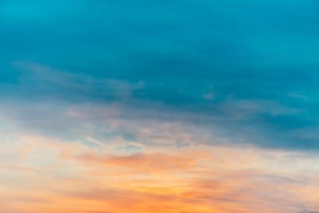 Sonnenuntergangshimmel mit orangegelben lichtwolken. bunter glatter blauer himmelsgradient. natürlicher hintergrund des sonnenaufgangs. erstaunlicher himmel am morgen. leicht bewölkte abendatmosphäre. wunderbares wetter im morgengrauen.