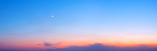 Sonnenuntergangshimmelpanorama mit einem jungen mond
