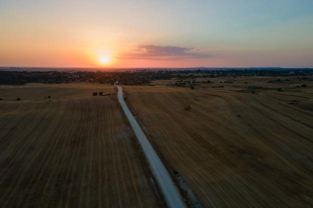 Sonnenuntergangslandschaft mit der stadt malpartida de caceres im hintergrund.