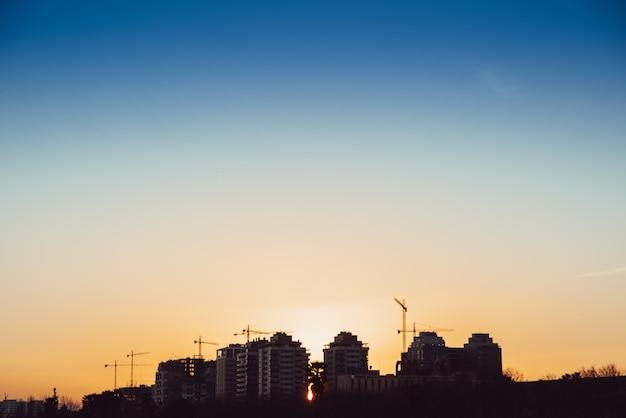 Sonnenuntergangssilhouette von gebäuden im bau mit maurerkränen.