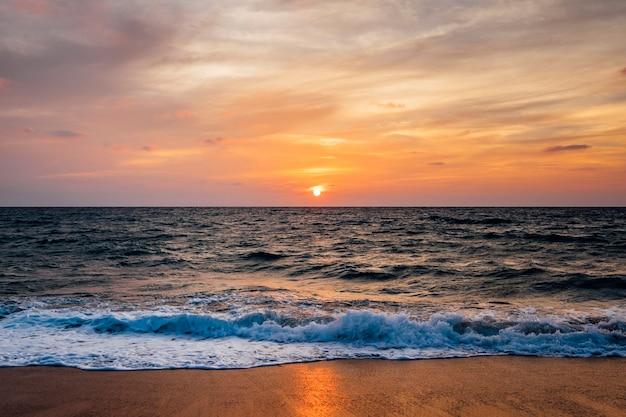 Sonnenuntergangsstrand und seewelle