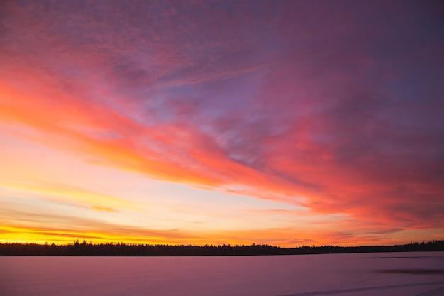 Sonnenuntergangswinterlandschaft mit schneebedeckter straße in den farben violett und rosa