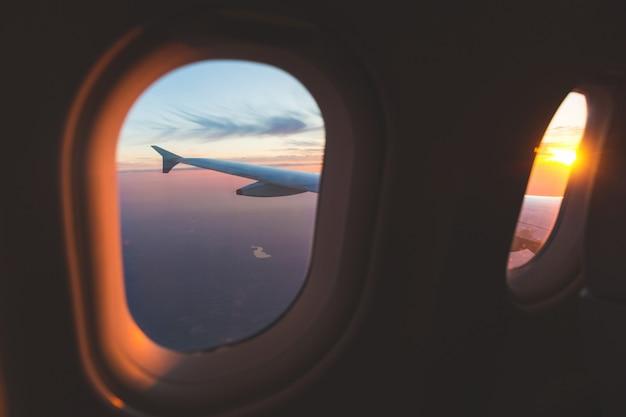 Sonnenuntergangvogelperspektive durch flugzeugfenster über flügeln