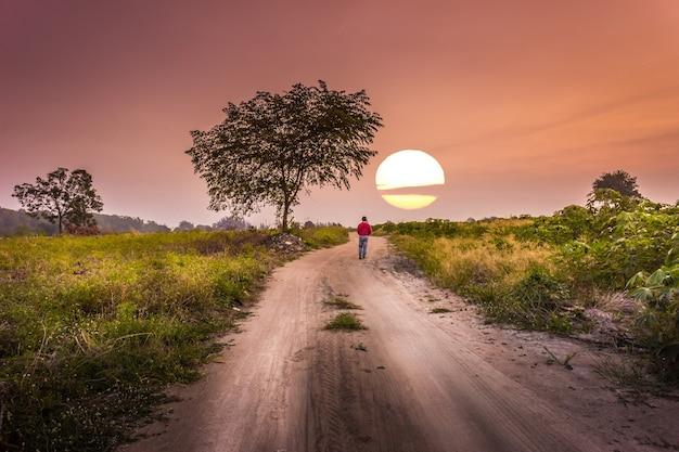 Sonnenuntergangzeit ein mann, der allein am landweg geht.