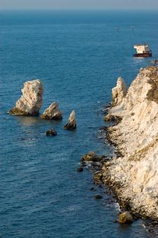 Sonnenuntergangzeit, versunkenes schiff, das auf der bank nahe der felsigen küstenlinie sitzt