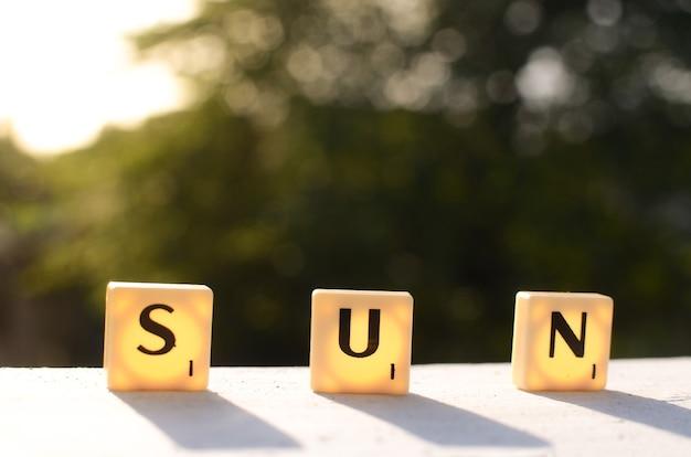 Sonnenwort mit buchstabenwürfel auf unschärfehintergrund