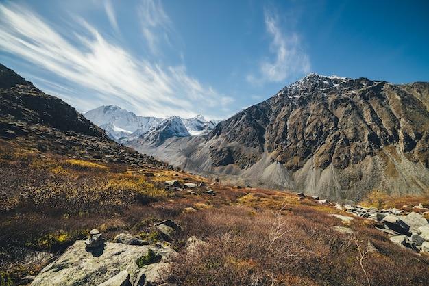 Sonnige herbstlandschaft mit hochlandtal und schneebedeckten hohen bergen unter blauem bewölktem himmel mit zirruswolken. stimmungsvolle berglandschaft mit sonnenbeschienenem tal zwischen felsigen bergen im herbst.