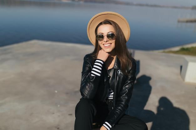 Sonnige junge vorbildliche mädchenfrau sitzen auf einer bank im herbsttag an der seewasserfront verkleidet