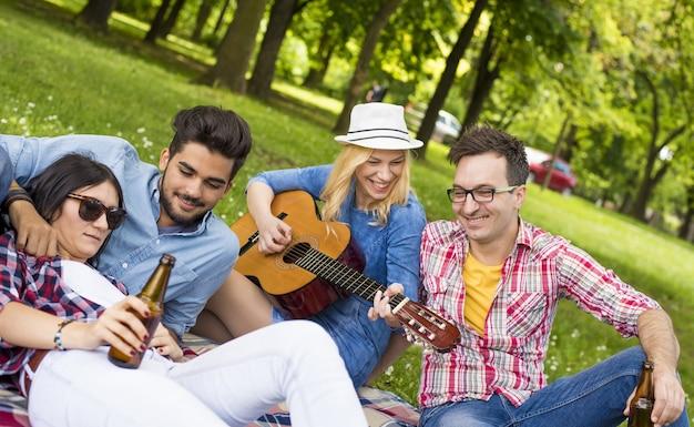Sonnige landschaft einer gruppe junger freunde, die spaß in einem park haben