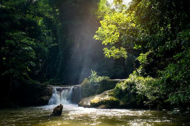 Sonnige strahlen des miniwasserfalls und des sonnenuntergangs