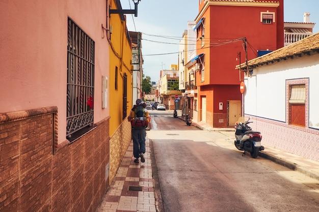 Sonnige straße am stadtrand von malaga und tourist mit rucksack. andalusien. spanien