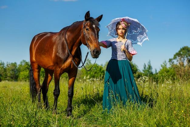 Sonnige tagesschönheit, die nahe bei dem pferd steht