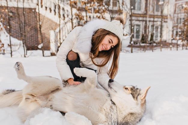 Sonniger gefrorener morgen der modischen genossen jungen frau, die mit husky-hund im schnee im freien spielt. schöne momente, wahre glückliche gefühle, süße haustiere, winterferien.