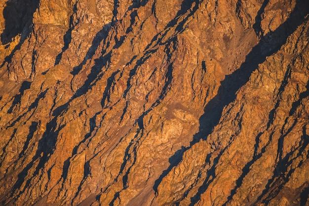 Sonniger naturhintergrund von rocky mountains im sonnenlicht. lebendige natürliche gebirgsbeschaffenheit der großen rauen felsen. voller rahmen der hellen riesigen schroffen oberfläche. rocky mountain nahaufnahme. ebene der glänzenden felsen auf sonnenuntergang.