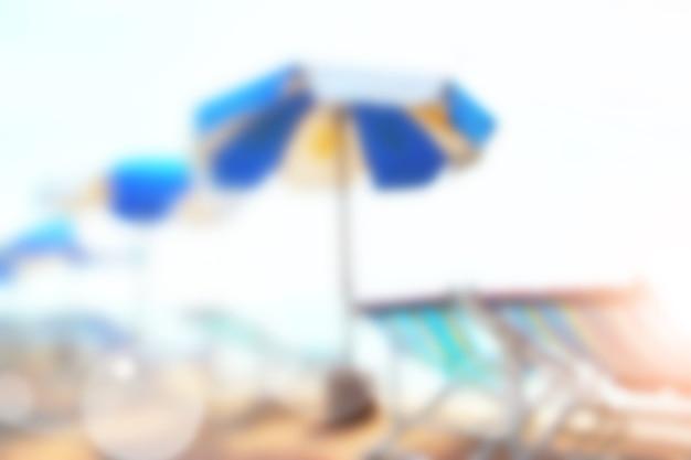 Sonniger sandstrand mit sonnenschirmen und stühlen unscharf - defokussierter, unscharfer hintergrund