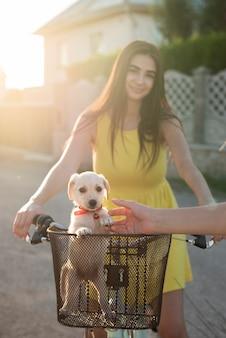 Sonniger schuss mit mädchen und ihrem hund auf dem fahrrad