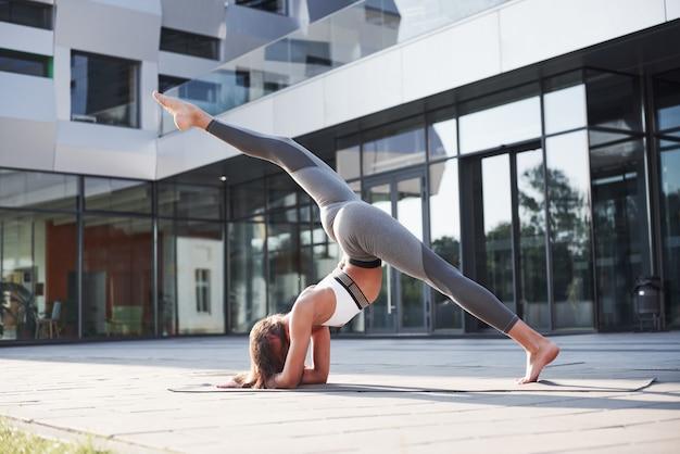 Sonniger sommermorgen. junge athletische frau, die handstand auf stadtparkstraße unter modernen städtischen gebäuden tut. übung im freien gesunden lebensstil