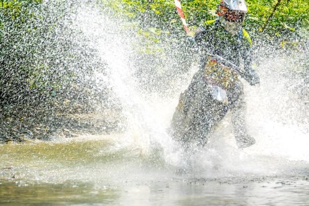 Sonniger sommertag im wald. enduro-athlet überwindet einen seichten bach mit vielen spritzern