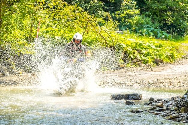 Sonniger sommertag im wald. enduro-athlet überwindet einen seichten bach mit vielen wasserspritzern