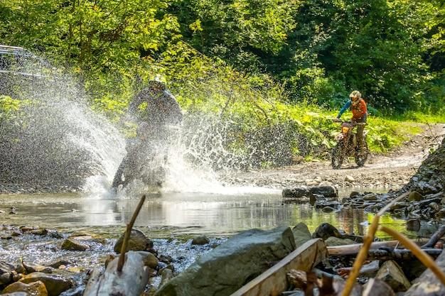 Sonniger sommertag im wald. zwei enduro-athleten überwinden einen seichten bach mit vielen wasserspritzern