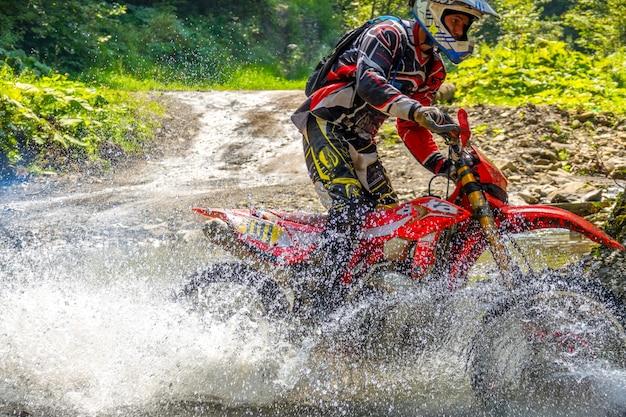 Sonniger sommertag und waldstrom. viel spritzwasser verbirgt ein enduro-motorrad. nahaufnahme