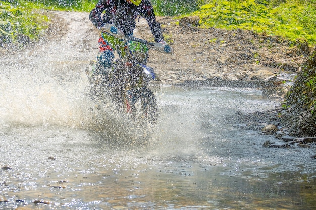 Sonniger sommertag und waldstrom. viel spritzwasser verbirgt ein enduro-motorrad