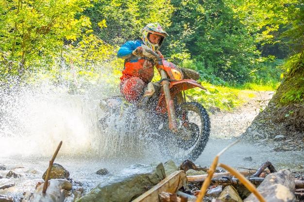 Sonniger sommertag. viel spritzwasser verbirgt ein enduro-motorrad, wenn ein sportler einen waldbach überquert. nahaufnahme