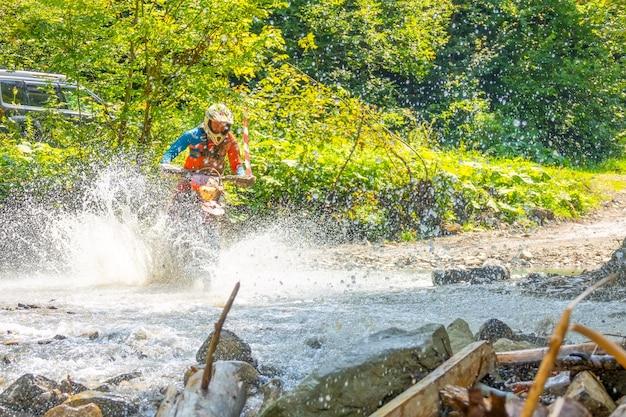 Sonniger sommertag. viel spritzwasser verbirgt ein enduro-motorrad, wenn ein sportler einen waldbach überquert