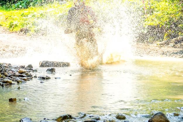 Sonniger sommertag. viel spritzwasser verbirgt enduro-sportler, wenn er einen waldbach überwindet