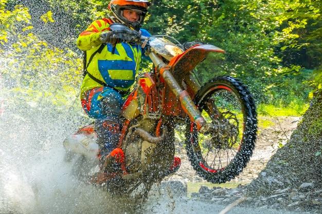 Sonniger sommertag. viel wasserspritzer, als ein sportler das enduro-motorrad ans hinterrad hob. nahaufnahme