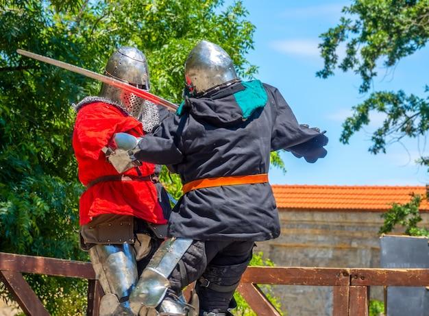 Sonniger sommertag. zwei mittelalterliche soldaten in rüstung und eisenhelmen, die mit schwertern kämpfen