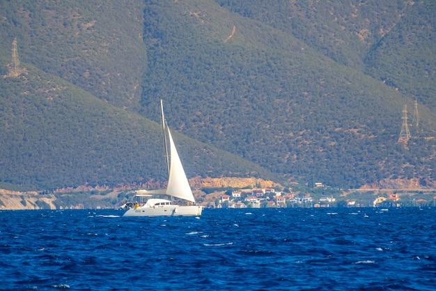 Sonniger sonnentag. hohe hügel am ufer. weiße yacht segelt mit segel