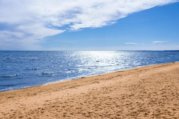 Sonniger strand, blaues meer unter blauem himmel mit weißen wolken, sommermeerblick.