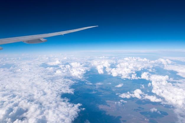 Sonniger tag der wolken und des himmels durch flugzeugfenster