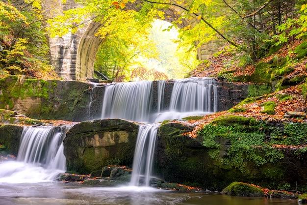 Sonniger tag im sommerwald. alte steinbrücke. kleiner fluss und mehrere natürliche wasserfälle