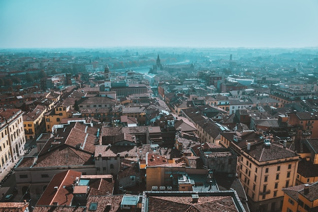 Sonniger tag in der altstadt, blick von oben auf rote dächer, historische gebäude, straßen und sehenswürdigkeiten, verona, italien
