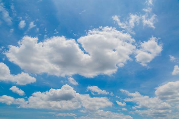 Sonniger tag mit weißen flaumigen wolken im blauen himmel