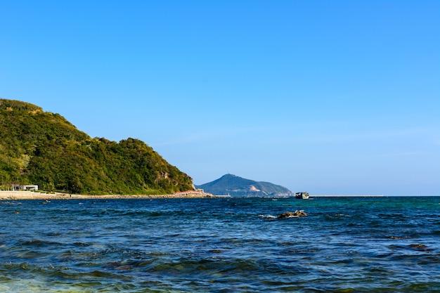 Sonniger tag, sand, klares türkisfarbenes meer, korallenriffe an der küste von xiaodonghai bay im südchinesischen meer. sanya, insel hainan, china. natur landschaft.