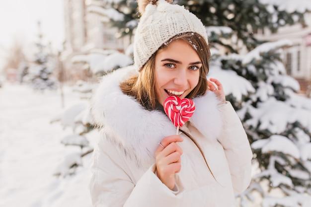 Sonniger wintermorgen auf der straße der reizenden jungen frau, die rosa lollypop leckt. glückliche zeit, positive gefühle der hübschen frau in der warmen weißen kleidung, strickmütze, die winterzeit genießt.