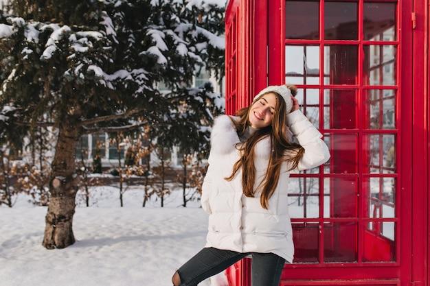 Sonniger wintermorgen, gute laune der charmanten frau in der warmen kleidung, die nahe rote telefonzelle auf straße genießt. kaltes wetter, warme, helle gefühle, voller schnee