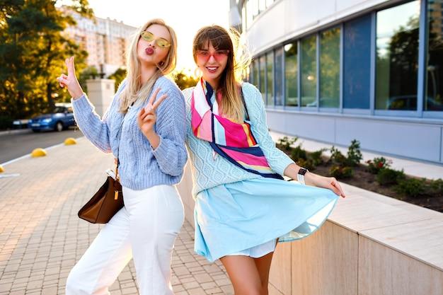 Sonniges lifestyle-porträt im freien von glücklichen, aufgeregten paaren eleganter mädchen, die gemeinsam spaß auf der straße haben, stilvolle vintage-outfits, pastellpullover und sonnenbrillen, passende accessoires, familienzeit.