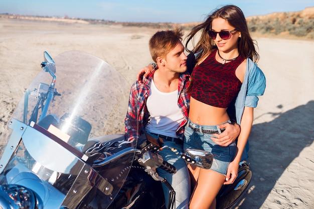 Sonniges porträt des lebensstils von jungen paarreitern, die zusammen auf sandstrand durch motorrad - reisekonzept sitzen. zwei personen und fahrrad. mode frau und mann umarmen und lächeln.
