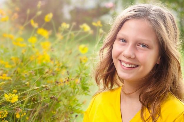 Sonniges sommerporträt des teenagermädchens mit gelben blumen
