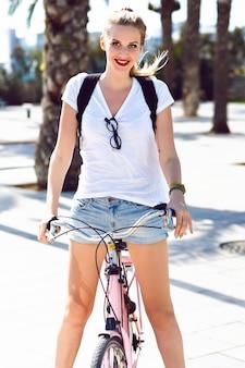 Sonniges sommerporträt im freien von freudigem glücklich lächelndem blondem mädchen, schreiend lachend und spaß habend, reitend retro vintage hipster fahrrad, freizeitkleidung, helles make-up, reisen, urlaubssommer.