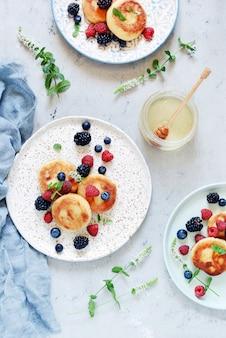 Sonntagsfrühstück mit käsekuchen, honig, frischen beeren und minze. hüttenkäsepfannkuchen oder klumpenstückchen verzierten honig und beeren in der platte auf blauer tischplatteansicht. gesund und diät frühstück.